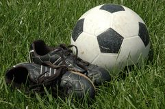 Soccer Shoes and Ball in Grass. Worn soccer shoes and ball laying in tall grass waiting for a game Royalty Free Stock Image