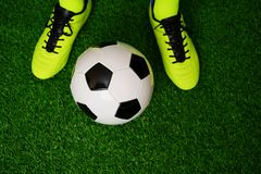 Soccer shoes and ball on the green grass. Close up royalty free stock photos