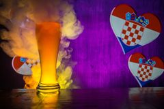 Soccer 2018. Single beer glass on table at dark toned foggy background. Support Croatia with beer concept. royalty free stock photo
