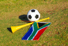 Soccer in South Africa. A colorful South African national flag, a black and white football and a yellow traditional Vuvuzela horn lying in the green grass after Royalty Free Stock Image