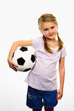 Soccer spirit. Cute girl playing football, happy child, young female goalkeeper enjoying sport game, holding ball, isolated portrait of a preteen smiling and Stock Image