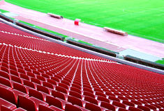 Soccer stadium. With red seats and green field Royalty Free Stock Photos