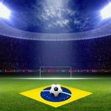 Soccer staduim, Brazil flag. Soccer ball, green soccer stadium, arena in night illuminated bright spotlights, soccer goal, Brazil flag stock photography