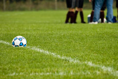 Soccer Strategy. Image of a soccer ball with a girl's soccer team conferring in the background.  Focus on the soccer ball with intentional shallow DOF Royalty Free Stock Photography