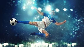 Soccer striker hits the ball with an acrobatic kick in the air on dark blue background. Football scene with a player who kicks the ball on the fly at the stadium stock photography