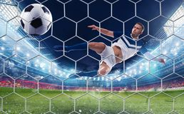 Soccer striker hits the ball with an jumping kick royalty free stock photo