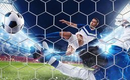 Soccer striker hits the ball with an jumping kick. Soccer striker hits the ball with an acrobatic jumping kick royalty free stock photography