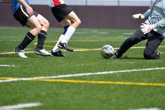 Soccer striker, sweeper and goalkeeper going for the ball Stock Photos