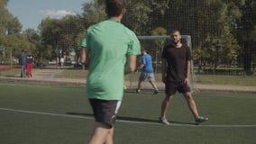 Soccer player scoring a goal after penalty kick. Soccer striker taking a penalty kick and scoring a goal during football match. Joyful teammates congratulating stock footage