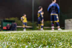 Soccer team in the background listening to coach. Royalty Free Stock Image
