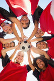 Soccer team with ball forming huddle against sky Royalty Free Stock Image
