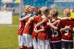 Soccer team huddling. Kids in red sportswear standing together and listening to coach. Junior football soccer tournament match royalty free stock photography