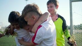 Soccer team of little boys is rejoicing by winning