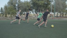 Soccer team scoring a goal in football game. Young street football players attacking opposing team, moving towards opponent goal with passing soccer ball in the stock video