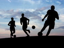 Soccer Training. Football players playing under the sunset Stock Photo