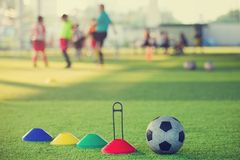 Soccer training Equipment on Artificial turf. Football and soccer training equipment on artificial turf with blurry players background. Soccer Academy stock images