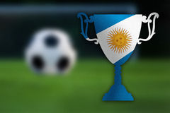 Soccer trophy with Argentina flag inside, ball and goal in the background. Stock Image
