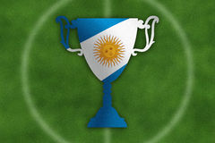 Soccer trophy with Argentina flag inside, field in the background. Stock Photography
