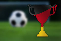 Soccer trophy with German flag inside, ball and goal in the background. Stock Photos
