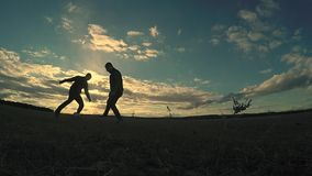 Soccer. Two men play soccer football silhouettes against the beautiful sport sky stock video