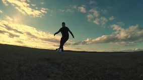 Soccer. Two men play soccer football silhouettes against sport the beautiful sky stock footage