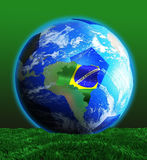 Soccer World Cup 2014. Soccer ball on the ground, surrounds the Earth where South America can be seen, and the map of Brasil covers the country Stock Photography