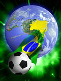 Soccer World Cup 2014. Soccer ball surfing on a Brazilian flag coming out of Brazil on an Earth globe Royalty Free Stock Photography