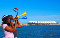 Soccer world cup fans. Two black South African soccer world cup 2010 supporters blowing their Vuvuzelas and waving the flag in front of the new Nelson Mandela royalty free stock photography