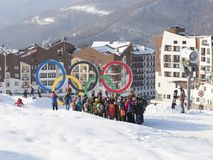 Tourist group photographed near the Olympic rings, Sochi. Sochi - March 29, 2017: A group of people are photographed near the Olympic rings in the Olympic ski Stock Image