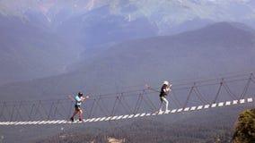 Sochi Rússia - em agosto de 2017 O cruzamento do abismo nas montanhas Os povos vão na ponte de corda através da falha Imagem de Stock
