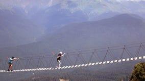 Sochi Rússia - em agosto de 2017 O cruzamento do abismo nas montanhas Os povos vão na ponte de corda através da falha Imagens de Stock