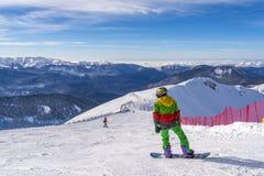 Sochi, Rússia, 10-01-2018 Estância de esqui de Rosa Khutor O Snowboarder está preparando-se para a raça que senta-se sobre Rose P fotografia de stock