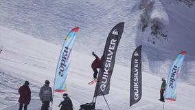 SOCHI, RUSIA - 2 DE ABRIL DE 2016: El Snowboarder salta del trampolín en estación de esquí Día asoleado MONTAÑAS NEVADO almacen de video