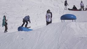 SOCHI, RUSIA - 2 DE ABRIL DE 2016: El Snowboarder salta del trampolín, hace tirón Estación de esquí asoleado Deporte activo metrajes