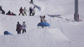 SOCHI, RUSIA - 2 DE ABRIL DE 2016: El Snowboarder salta sobre el trampolín Estación de esquí Truco extremo Deporte activo almacen de video