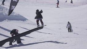 SOCHI, RUSIA - 2 DE ABRIL DE 2016: La diapositiva del Snowboarder en el carril, hace salto de altura Estación de esquí Día asolea metrajes
