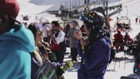 SOCHI, RUSIA - 2 DE ABRIL DE 2016: La muchacha en casco almuerza adentro acampar entre otras personas Estación de esquí holidays metrajes