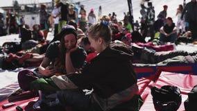 SOCHI, RUSIA - 2 DE ABRIL DE 2016: Las muchachas se relajan adentro acampan entre otras personas Estación de esquí holidays Sonri almacen de video