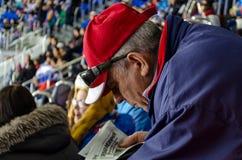 Sochi Rusia - 16 de febrero de 2014: Fans que leen un periódico durante una rotura en el partido fotos de archivo