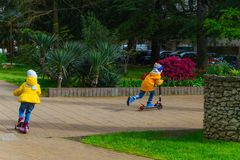 SOCHI,RUSSIA,  18 APRIL 2019 - boy and girl  in a bright yellow jackets riding   scooters in the park. Boy and girl  in a bright yellow jackets riding   scooters royalty free stock image