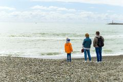 SOCHI,RUSSIA,  18 APRIL 2019 - man, woman and their child stand with backs to the camera on the Black sea shore in cloudy weather. Man, woman and their child stock photos