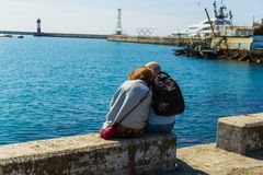 SOCHI,RUSSIA,23 APRIL 2019 - romantic couple sitting on the Black Sea beach, man and woman sitting back to the camera on the sea. Romantic couple sitting on the royalty free stock images