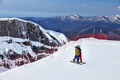 Sochi, Russia - April 1, 2014: Young couple stands embracing on ski track in Gorky Gorod mountain ski resort on snowy Caucasus royalty free stock photos