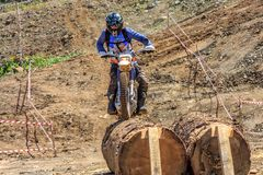 Sochi, Russia - August 16, 2014: Enduro motorbike racer overcomes obstacle on off-road terrain track at motocross competition on royalty free stock photo