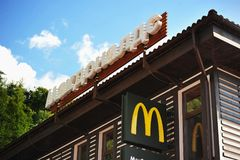 Sign and the logo of McDonald`s in mountain forest background. Sochi, Russia - July 10, 2017: the sign and the logo of McDonald`s in mountain forest background royalty free stock photography