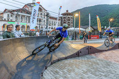 Sochi, Russia - July 11, 2015: Sportsmen bikers on outdoor pump track at Gorky Gorod mountain resort. Bike riders run pursuit race.  Stock Images