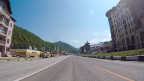 Sochi, Russia - June 2018: Asphalt road panorama on sunny summer day. Scene. Route in beautiful nature landscape with. Sun, blue sky, green grass stock footage