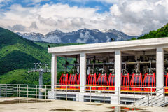Sochi, Russia - May 23, 2014: Scenic sunny landscape of parked red passenger cabins at RusSki Gorki Ski Jumping Center surrounded Stock Images