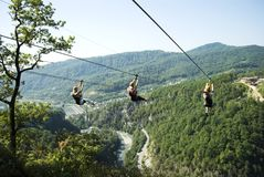 Girls ride on the attraction. SOCHI, RUSSIA - SEPTEMBER 19, 2017: Girls ride on the attraction `ZipLine` in Ahshtyrsky gorge Stock Photo