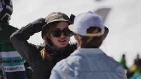 SOCHI RYSSLAND - APRIL 2, 2016: Unga flickan i solglasögon talar med mannen campar in semesterorten skidar snowboarders arkivfilmer